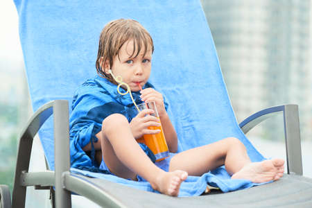 Kid drinking juice after swimming Stock Photo