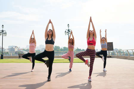 Slim ethnic women in sportswear practicing yoga asana together on paved seafront of city in sunlight