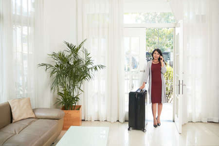 Young Asian businesswoman talking on mobile phone while entering to the modern house with her luggage, she has a business trip