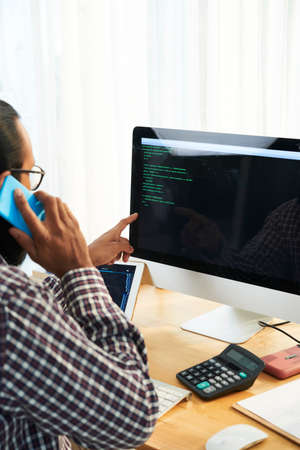 Modern it developer sitting in front of computer screen with code and talking by smartphone at workplace