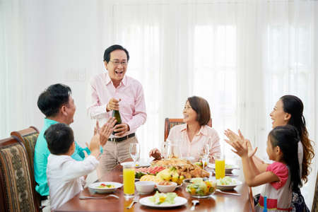Group of ethnic adult people and kids enjoying delicious meal at table with man opening bottle of champagne