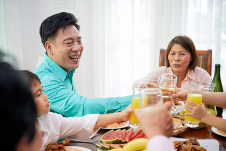 Happy Asian family with glasses toasting while having celebration at home gathering at dinner