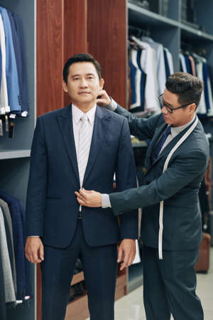 Menswear shop assistant helping middle-aged Vietnamese man to choose perfect suit Banco de Imagens