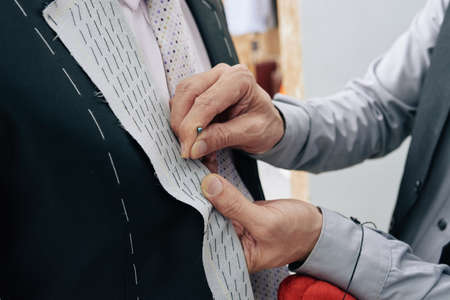 Close-up image of tailor making wedding suit for man