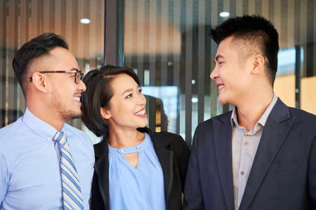 Smiling Asian business people looking at their successful colleague with admiration