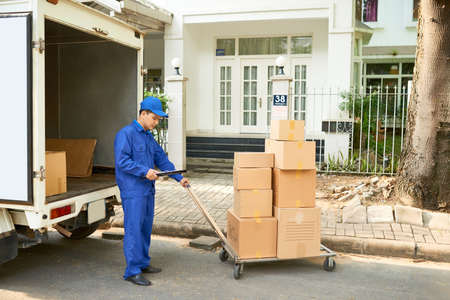 Delivery service worker loading his truck with cardboard boxes