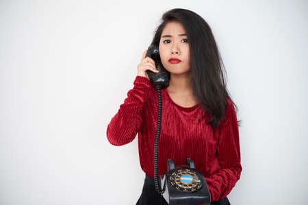 Portrait of Asian pretty young girl in red blouse has a conversation on old fashioned phone isolated on white background Stock Photo