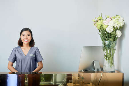 Portrait of Asian woman in uniform standing behind the reception and smiling at spa salon 스톡 콘텐츠