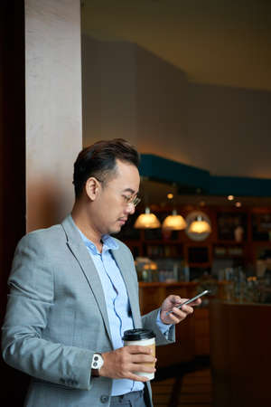 Asian businessman drinking coffee and checking massages in his phone Stock Photo