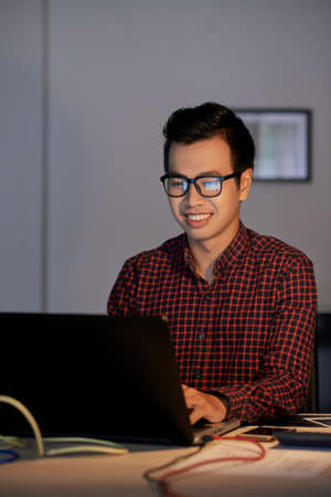 Portrait of positive smiling web designer working on laptop 免版税图像