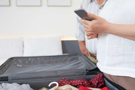 Hands of senior woman checking list on smartphone when packing for vacations Stock Photo