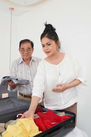 Senior Asian couple unpacking suitcase in hotel room Archivio Fotografico