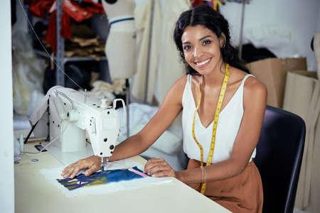 Schöne lächelnde junge Näherin, die an der Nähmaschine in der Werkstatt arbeitet