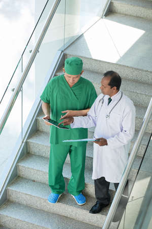 Doctors walking down the stairs and discussing medical report on tablet computer