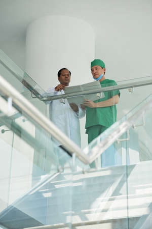 Serious surgeon and anesthesiologist reading medical history of patient before performing surgery