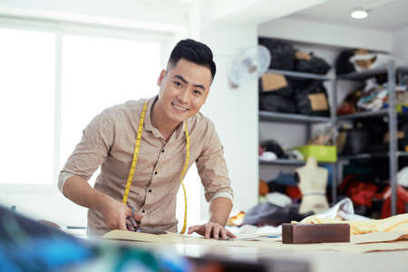 Positive young Asian tailor working cutting pattern for new model of dress Stock Photo