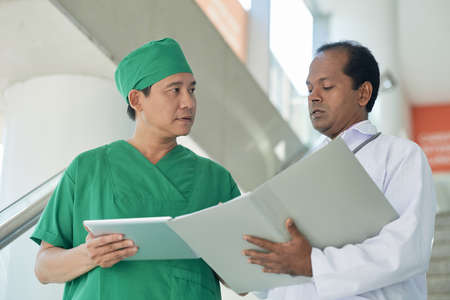 Serious chief doctor and surgeon reading medical record of new patient Stock Photo