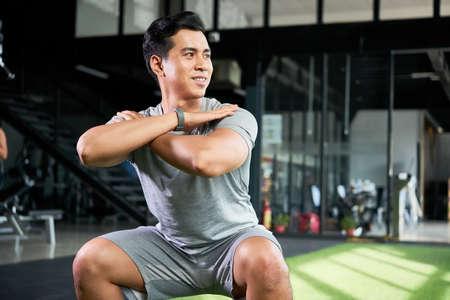 Cheerful man exercising in gym Standard-Bild