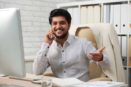 Portrait of smiling Indian businessman with smartphone