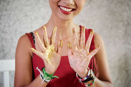 Close-up of woman standing with her hands covered with golden sequins and smiling, she finished her artwork