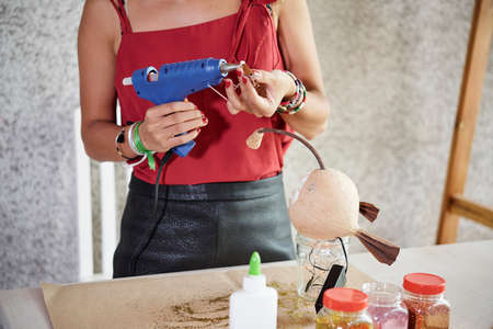 Young woman standing and gluing details for her designer thing with electric hot glue gun in workshop Reklamní fotografie