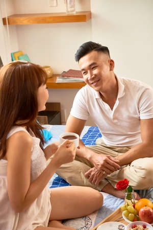 Smiling Asian man sitting on bed and talking to his girlfriend while she having breakfast in bedroom
