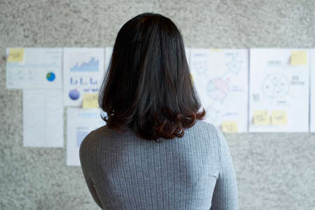 Rear view of businesswoman with dark short hair looking at financial charts on the wall at office