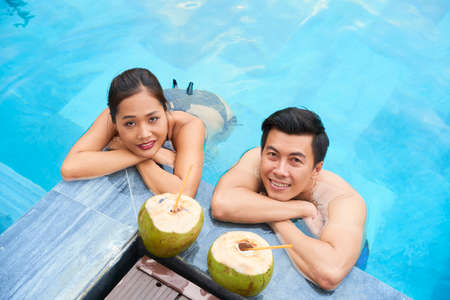Portait of Asian young couple near the poolside smiling and drinking coconuts outdoor at resort