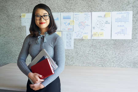 Portrait of Asian young teacher in eyeglasses standing with books and laptop in her hands at classroom with different charts and graphs hanging on the wall in the background 版權商用圖片