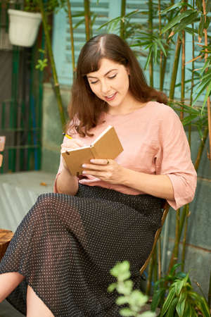 Positive beautiful woman sitting outdoors and writing her thoughts and ideas in diary