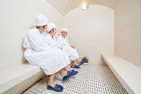 Group of young Asian women wearing bathrobes sitting together and talking while having sauna session Standard-Bild
