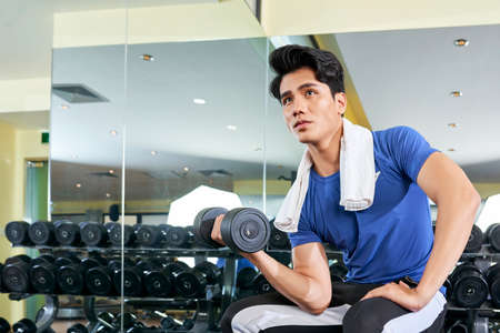 Young Asian sportsman sitting and holding dumbbell in his hand, he training his muscles in gym