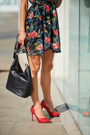 Crop female in floral dress and red high heeled shoes standing on pavement near shop window on city street Stock Photo