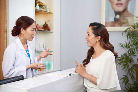 Beautiful mature woman standing and discussing with receptionist some procedure of plastic surgery in clinic Stockfoto