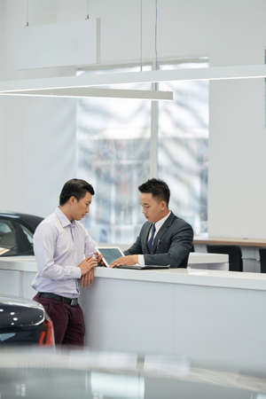 Salesman and customer reading leasing contract