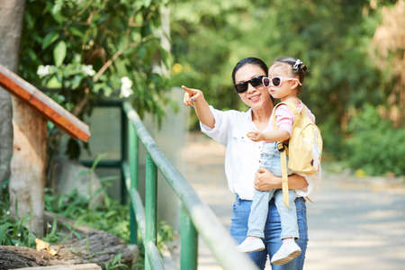 Smiling Vietnamese woman in sunglasses carrying her little daughter and showing her plays and trees in park Фото со стока