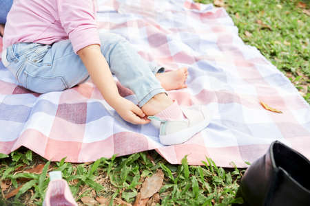 Close-up image of little girl taking off sneakers and socks when resting on blanket in park
