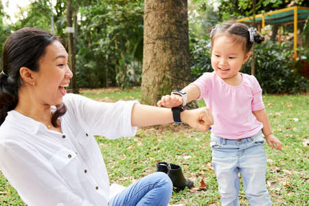 Little Asian girl excites to wear smart watches just like her mother Banco de Imagens