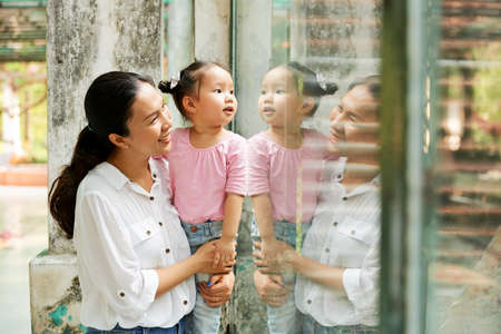 Mother and her curious daughter standing at glass window in zoo and looking at animals