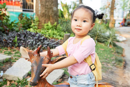 Positive little Asian girl sitting on wooden deer when playing in park