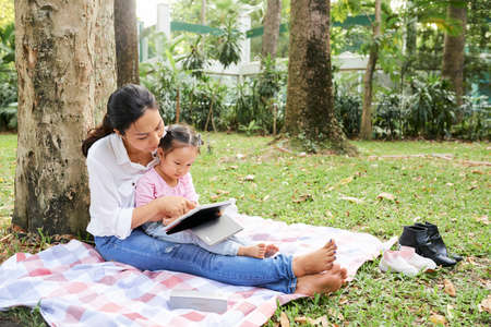 Vietnamese young woman and her little daughter sitting under tree in park using educational application on tablet computer
