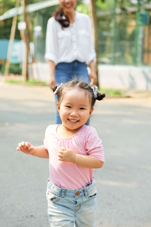 Cheerful adorable little girl running , her mother standing in background