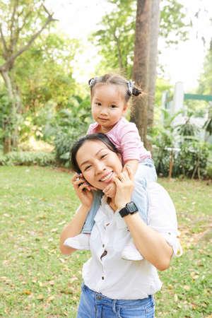 Positive Vietnamese woman spending summer day with her little daughter in park 版權商用圖片