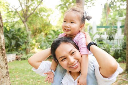 Pretty young Asian woman spending time with her child in park on summer day Imagens