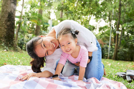 Happy young Asian woman and her smiling daughter playing in park on summer day