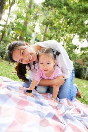 Cheerful Vietnamese mother and daughter playing on blanket in city park 版權商用圖片