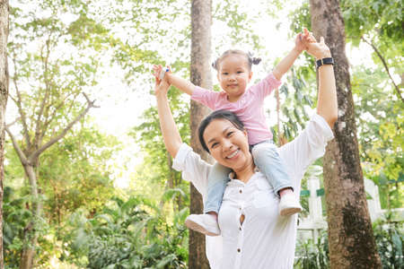 Happy Asian woman giving piggyback ride to daughter and rising hands to express joy
