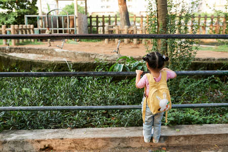 Rear view of little girl with small yellow backpack climbing on railing in park
