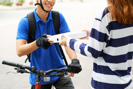 Smiling food delivery courier giving pizza box to female client