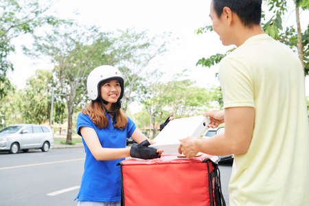 Cheerful pretty young Asian woman in helmet delivering small pizza tp young man
